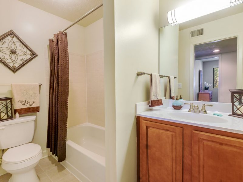 This image shows the bathroom area featuring the modern brushed nickel fixtures and a shower curtain for the bathtub.