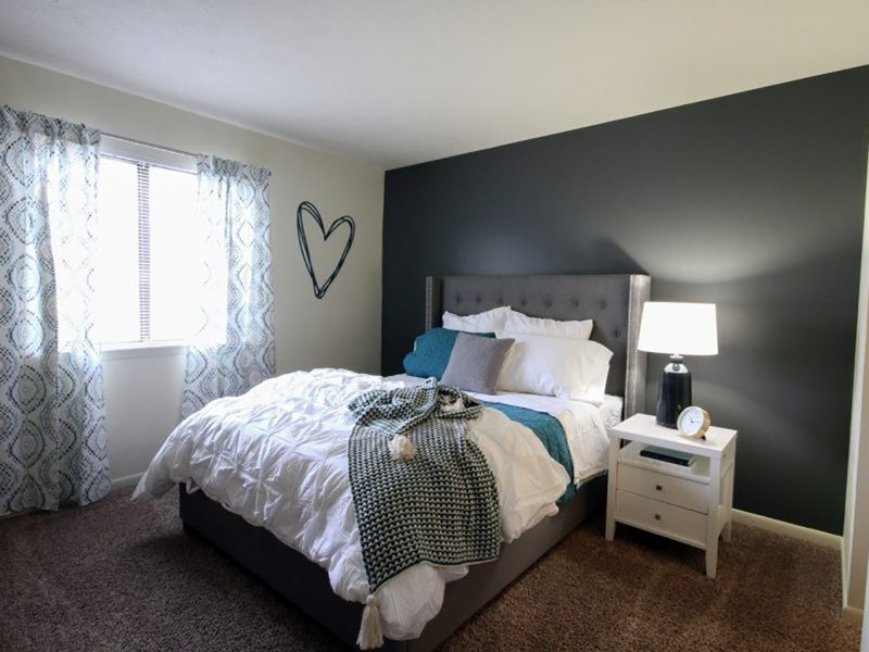 This image shows the premium apartment feature, specifically the bedroom area showing the warm tone and ideal bed set.