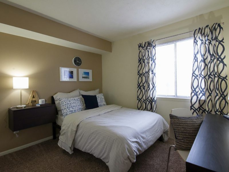 This image showcases the bedroom area featuring the caramel wall color, a mini working station, and cozy bedding.