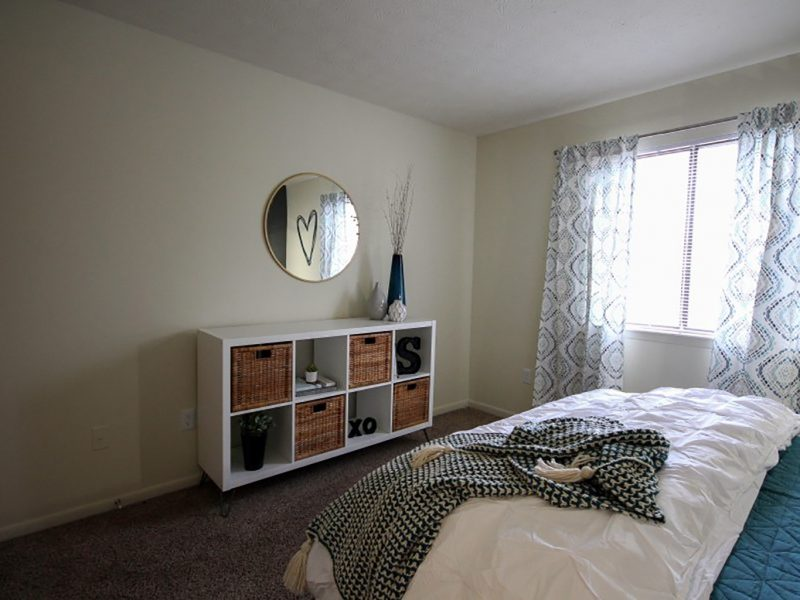 This image shows the bedroom area showcasing its minimal wall decor, comfortable beddings, and a window overlooking the view of TGM Shadeland Station Apartments.