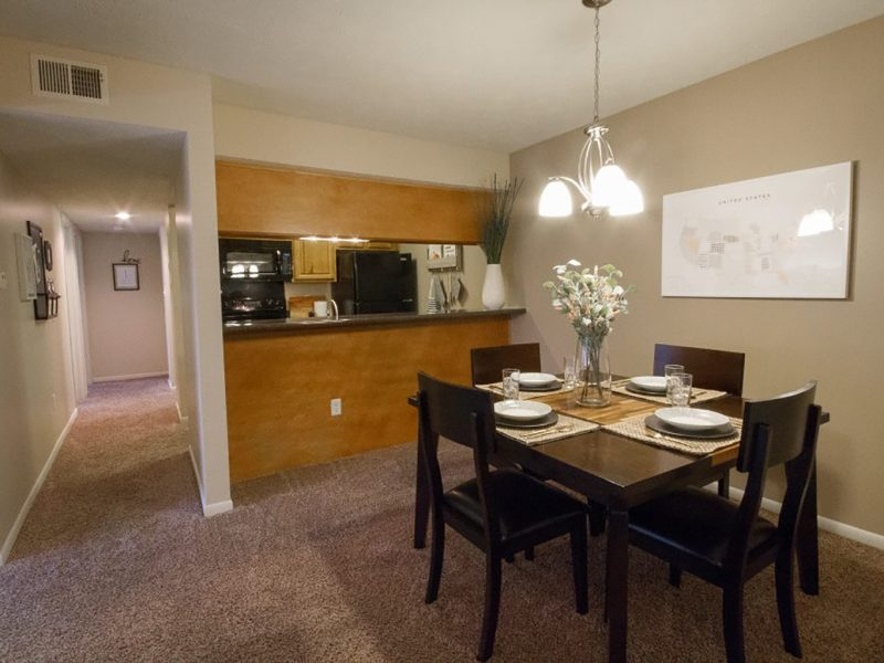 This image shows the premium apartment feature, particularly the formal dining room area featuring the elegant chandelier and an ideal dining set.