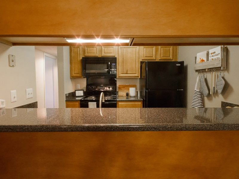 This image shows the breakfast bar featuring the trendy kitchen cabinets with granite-inspired countertops.