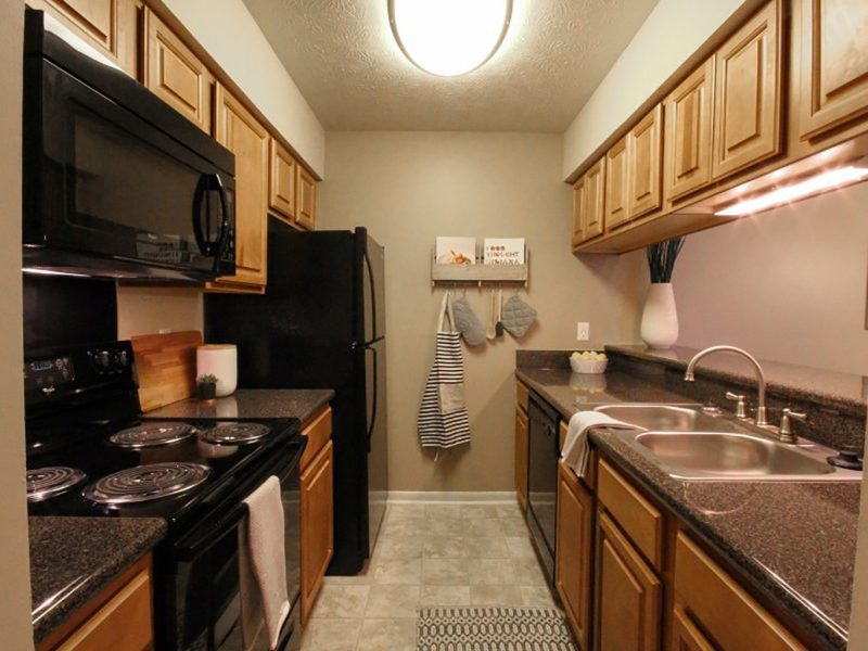 This image shows the premium apartment feature, especially the elegant kitchen island featuring the fully equipped kitchen with black Whirlpool appliances.